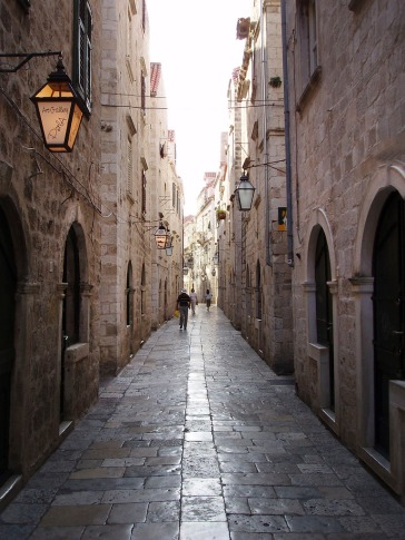 The historic old town of Dubrovnik, walking the quiet city streets at first light in the morning - bathed in the shadows walking between historic buildings some dating back to the 14th century.