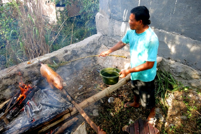 Using a palm frond to baste the skin with some oil towards the end to help crisp up the skin and finish the cooking process.